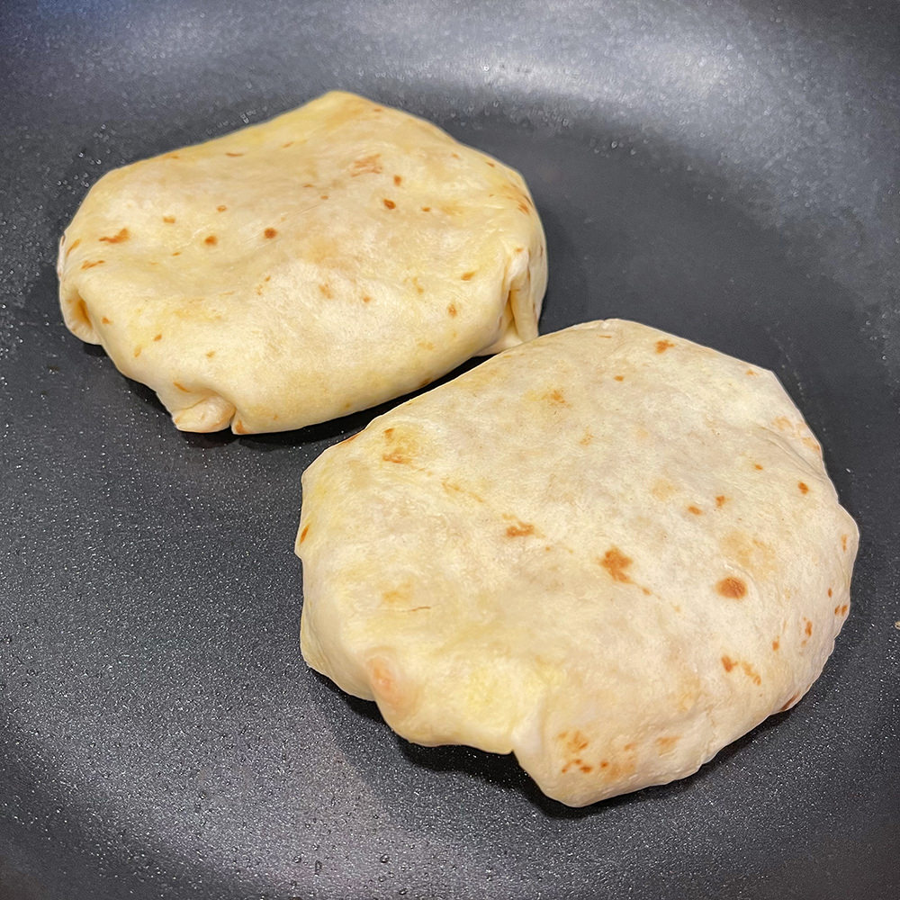 The torilla wrapped around the ingredients and flipped in the pan.