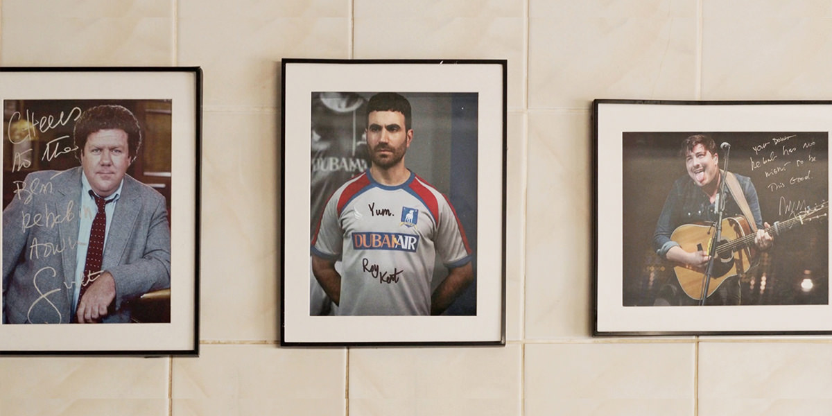Celebrity photos at a kebab shop with a photo of Roy Kent signed YUM!