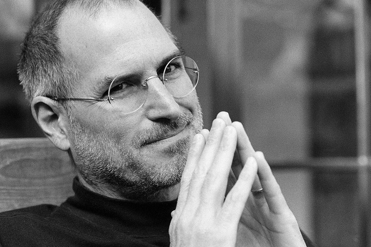 Steve Jobs smiling and looking like a genius.