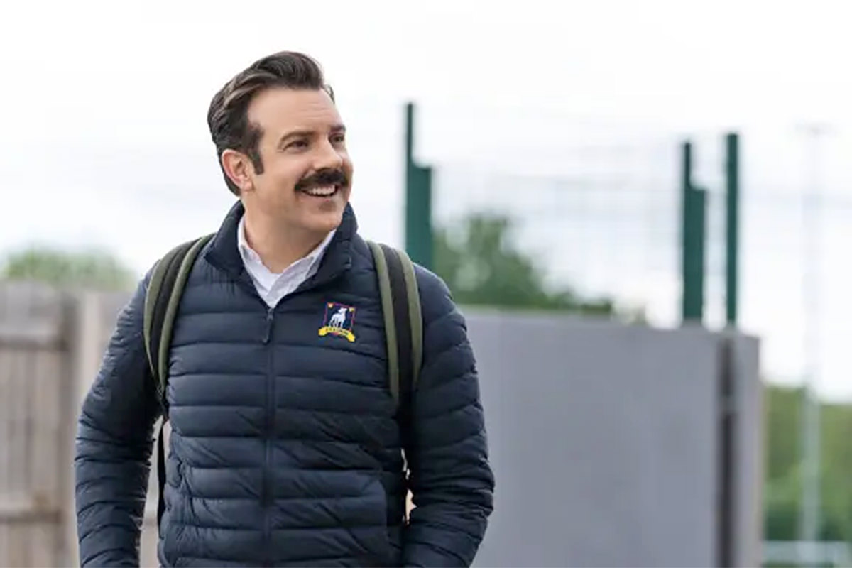 Ted Lasso walking and smiling on a chilly London day.