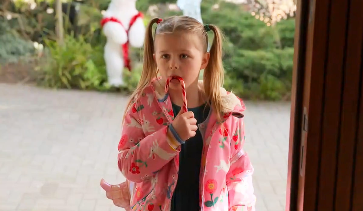 Phoebe with a candy cane at Keeley's door.